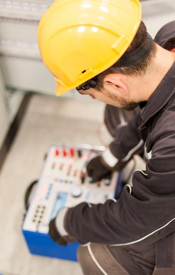 El ingeniero del mantenimiento examina el sistema con equipmen determinados de la prueba de la retransmisión imagen de archivo
