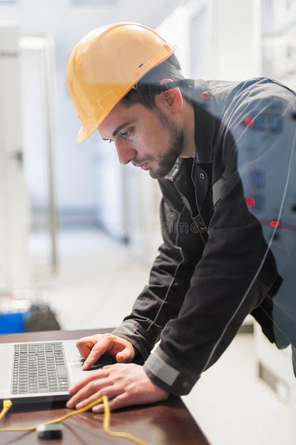 El ingeniero del mantenimiento examina el sistema de protección de la retransmisión con el ordenador portátil imagen de archivo libre de regalías