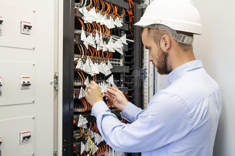 El ingeniero del técnico conecta fibras ópticas en el interruptor de la comunicación en centro de datos Hombre del servicio en da fotografía de archivo libre de regalías