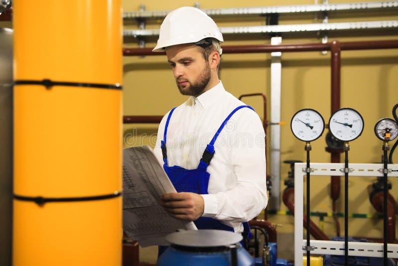 El ingeniero del técnico lee el dibujo en la estación de calefacción de la caldera fotos de archivo libres de regalías