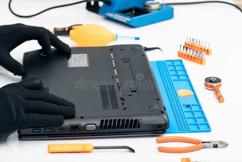 El ingeniero desmonta los detalles de un ordenador portátil quebrado para la reparación fotografía de archivo