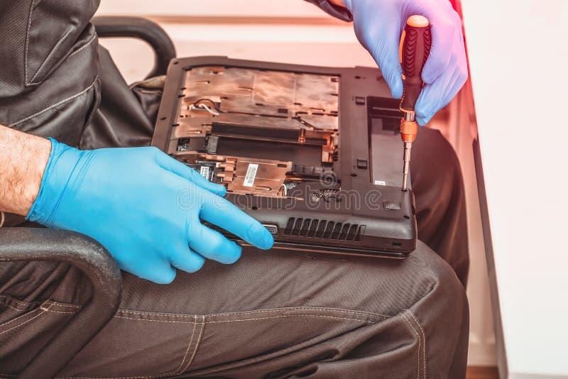 El ingeniero desmonta los detalles de un ordenador port?til quebrado para la reparaci?n imagen de archivo