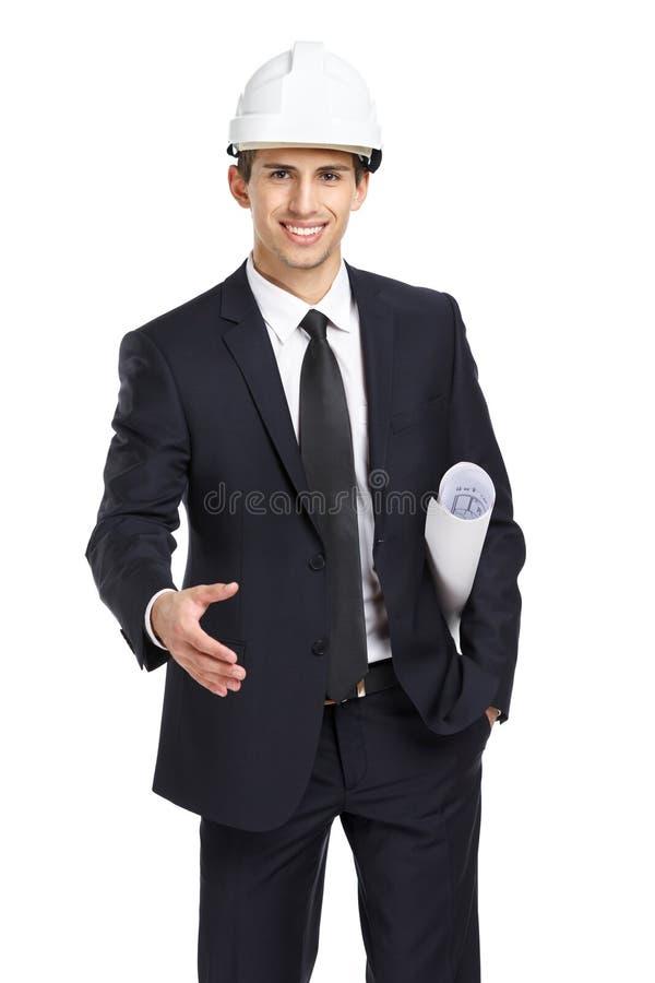 El ingeniero en apretón de manos del casco gesticula y da el modelo foto de archivo