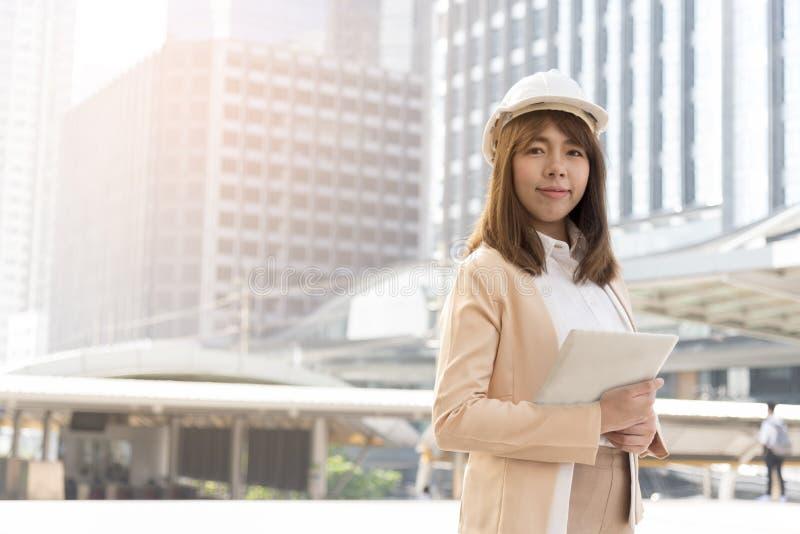 El ingeniero hermoso de la felicidad lleva la situación blanca del casco de seguridad delante del edificio grande en la ciudad imagen de archivo libre de regalías