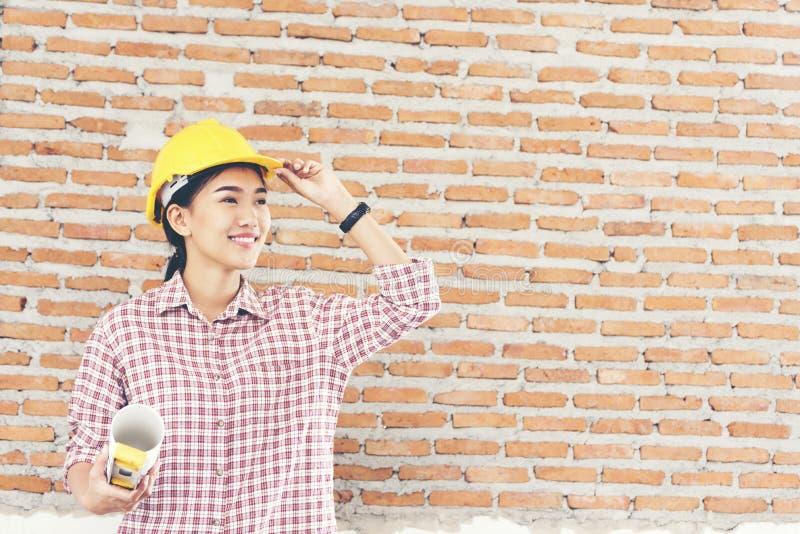 El ingeniero hermoso joven que trabaja llevando a cabo planes del edificio lleva el casco amarillo imágenes de archivo libres de regalías