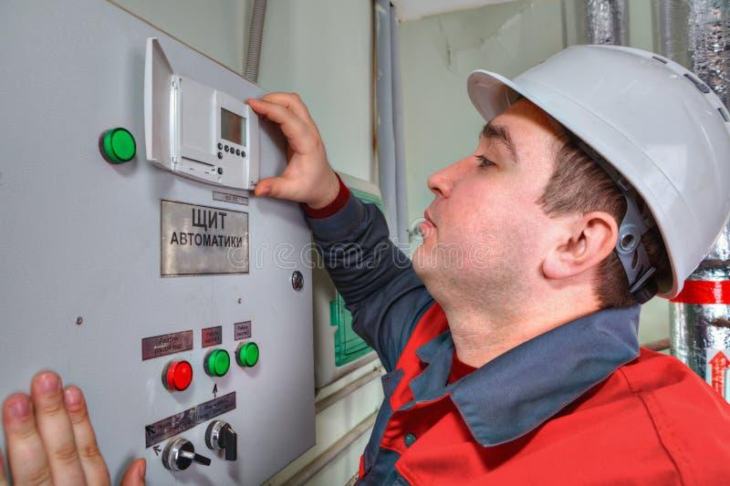 El ingeniero industrial lee las lecturas en el panel del dispositivo de distribución foto de archivo