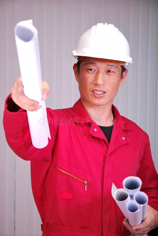 El ingeniero joven, el trabajador en uniforme rojo foto de archivo