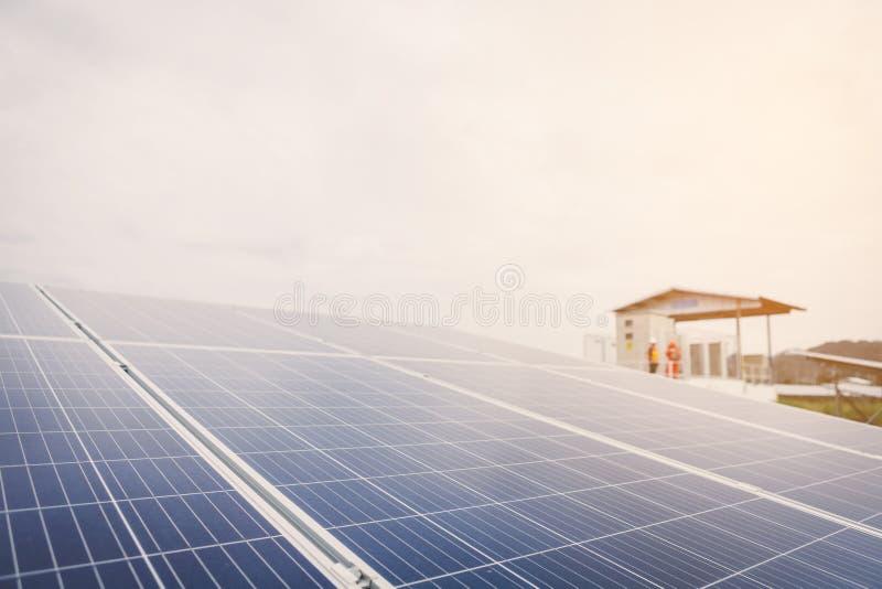 El ingeniero o el electricista examina y comprobando el equipo solar; tecnología elegante para la operación de la planta de ene imagen de archivo