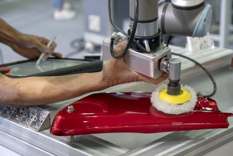 El ingeniero puso el brazo del robot en el pulido de la parte automotriz fotos de archivo