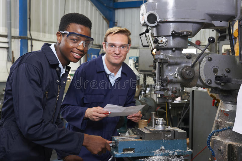 El ingeniero Showing Apprentice How a utilizar perfora adentro la fábrica imagen de archivo