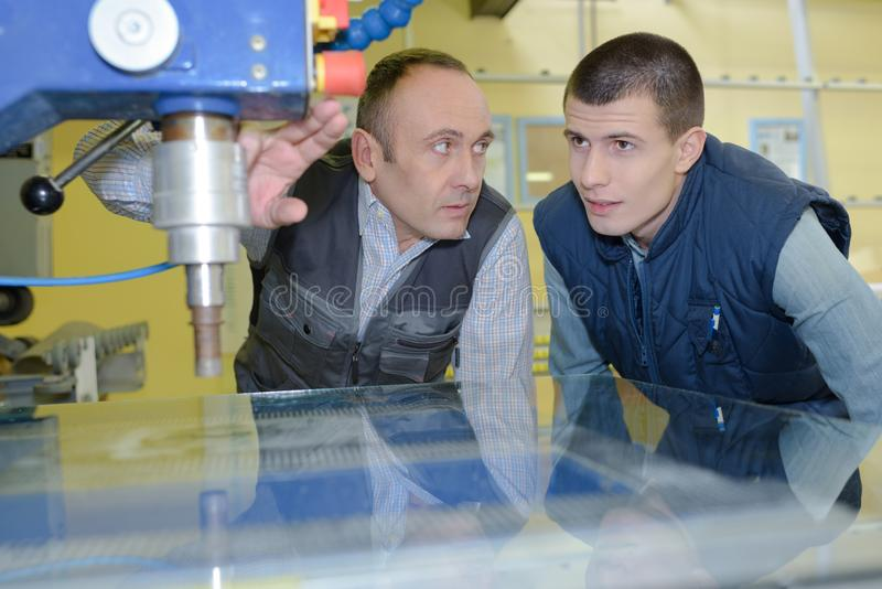 El ingeniero Showing Apprentice How a utilizar perfora adentro la f?brica fotos de archivo