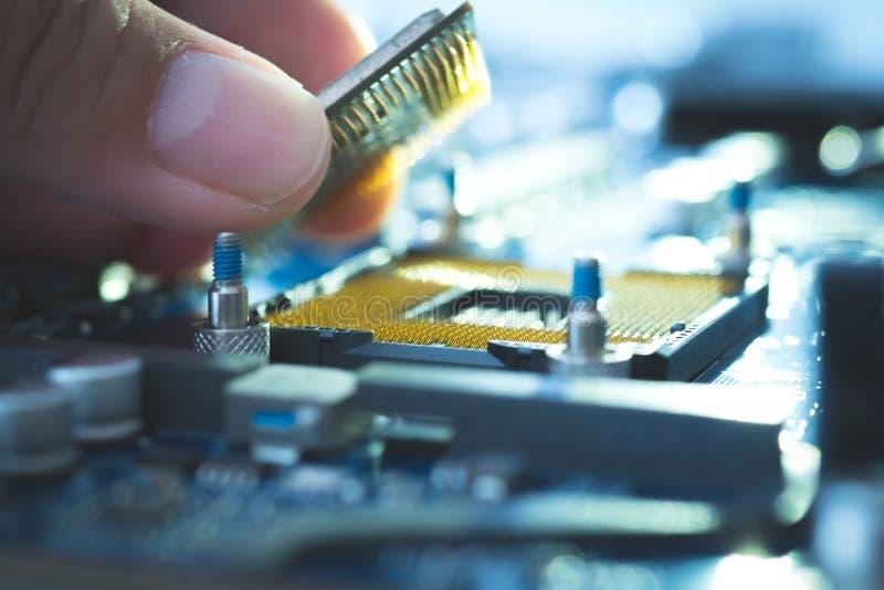 El ingeniero Technician enchufa el microprocesador de la CPU del ordenador al mothe foto de archivo