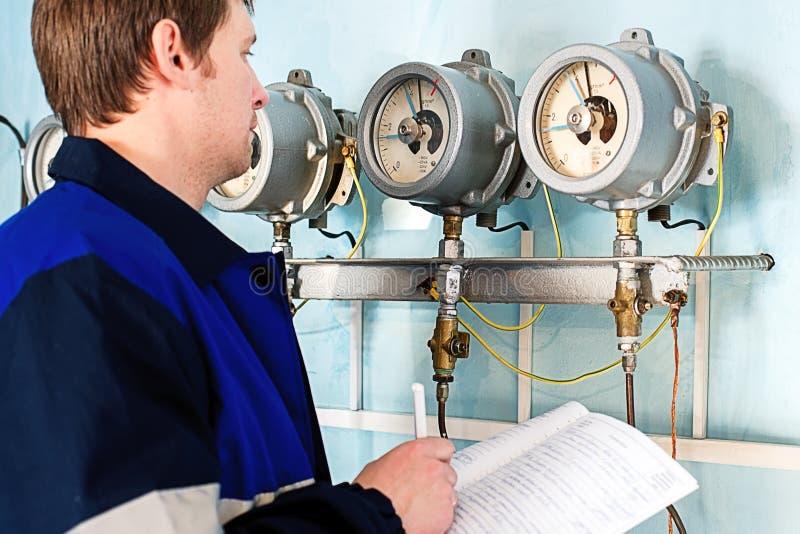 El ingeniero, trabajador registra lecturas de sensores y de indicadores de presión Control del abastecimiento de agua y del siste imagen de archivo libre de regalías