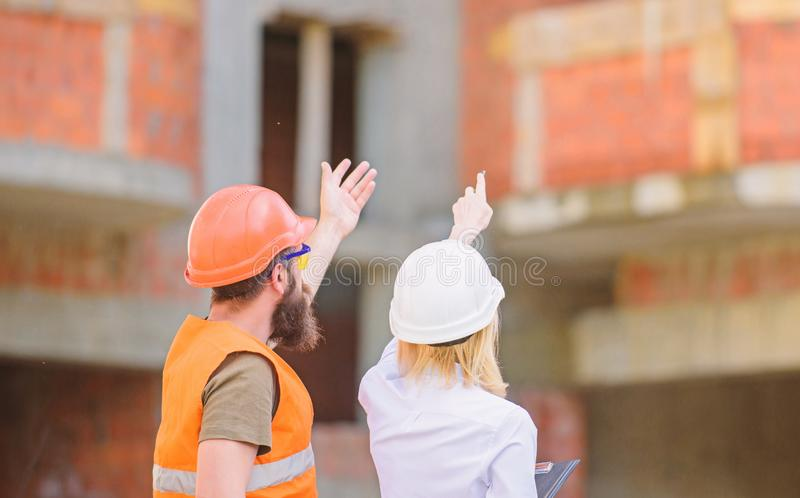 El ingeniero y el constructor de la mujer comunican el emplazamiento de la obra Relaciones entre los clientes de la construcci?n  fotografía de archivo libre de regalías
