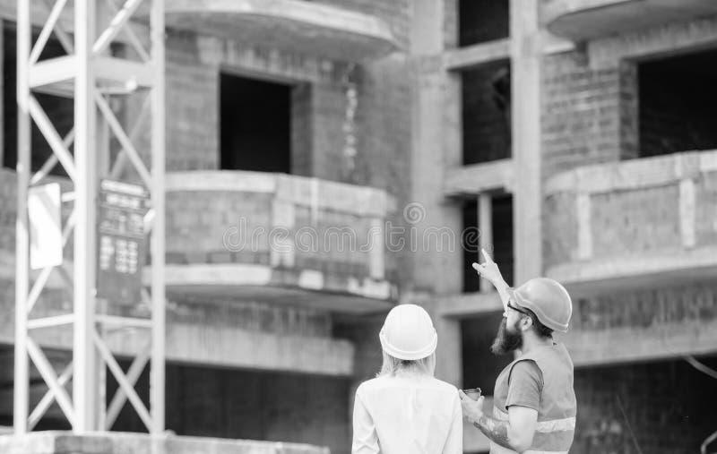 El ingeniero y el constructor de la mujer comunican en el emplazamiento de la obra Relaciones entre los clientes de la construcci fotografía de archivo libre de regalías