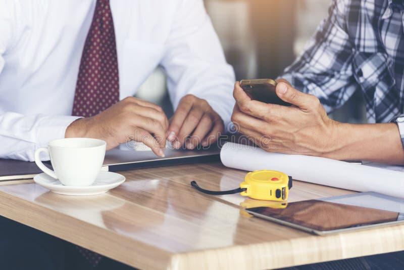El ingeniero y el hombre de negocios elegantes discuten en proyecto Reunión al aire libre de trabajo del equipo Casco blanco de l fotos de archivo libres de regalías