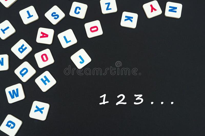 El inglés coloreó letras cuadradas dispersadas en fondo negro con los números 123 imágenes de archivo libres de regalías