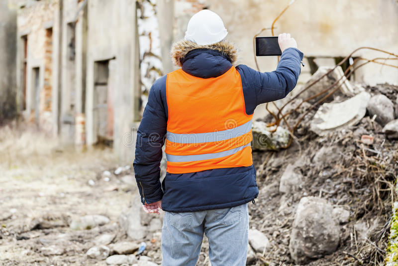 El inspector de construcción filmado con la tableta dilapidó edificio imagen de archivo