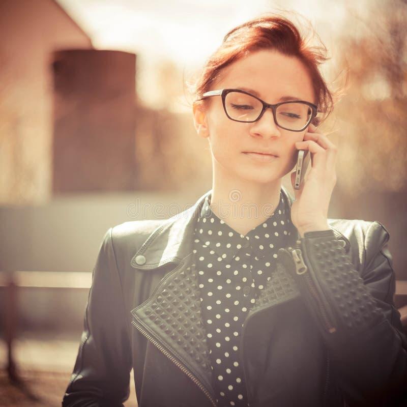 El instagram estilizado colorized el retrato de la moda del vintage de los vidrios que llevaban de una mujer atractiva joven con e imagen de archivo libre de regalías