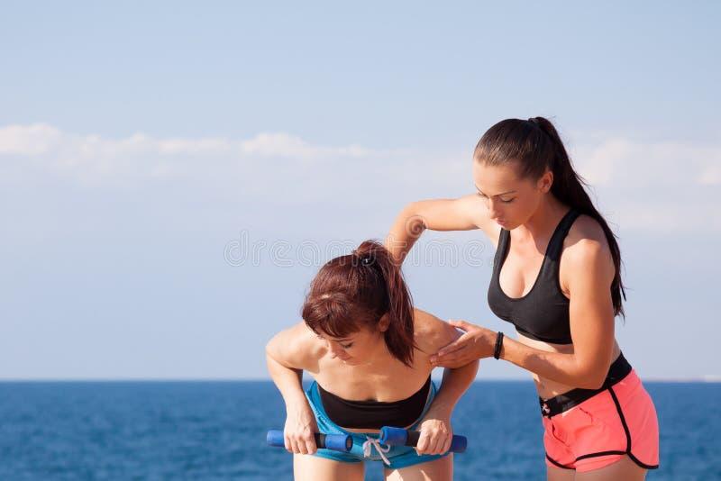 El instructor ayuda a la muchacha a hacer los ejercicios fotos de archivo