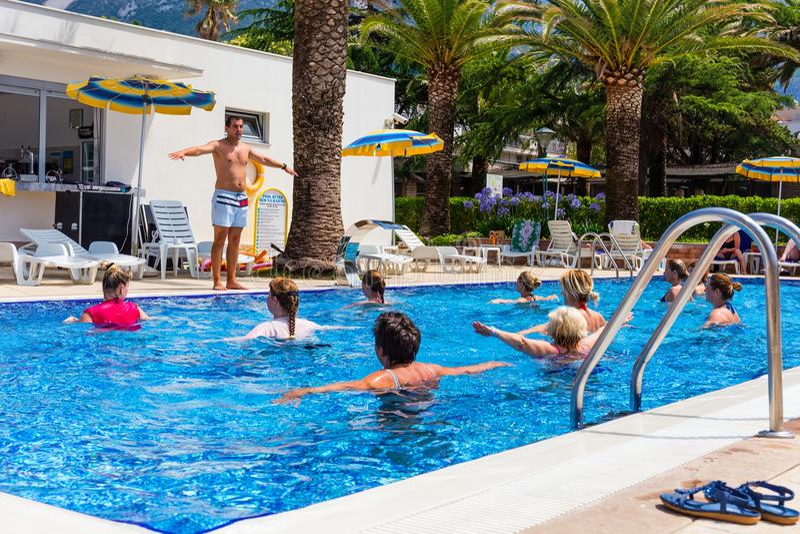 El instructor de la aptitud celebra una clase de aeróbicos de la aguamarina en el hotel foto de archivo
