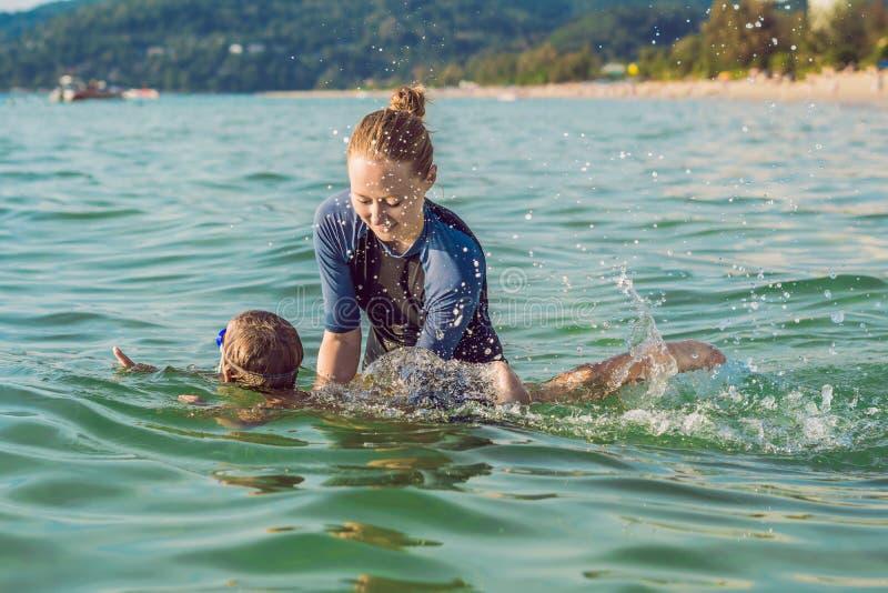 El instructor de la natación de la mujer para los niños está enseñando a un muchacho feliz a nadar en el mar fotografía de archivo libre de regalías
