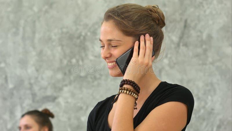 El instructor de la yoga habla en el teléfono después de entrenar fotografía de archivo