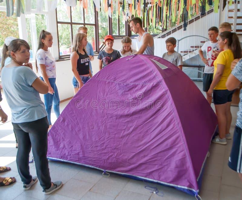 El instructor enseña a adolescencias a montar una tienda en el campamento de verano fotografía de archivo libre de regalías