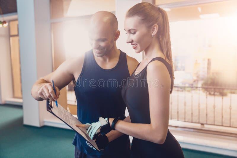 El instructor escribe un programa de fitness que entrena a la muchacha imagen de archivo