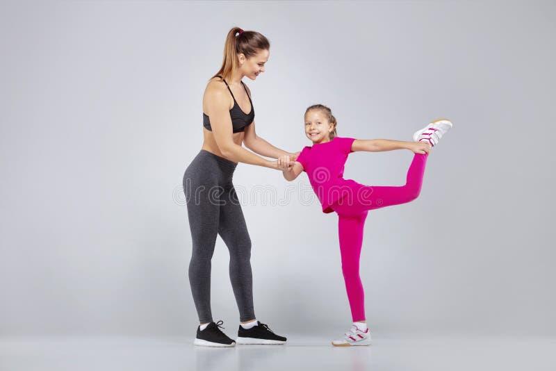 El instructor femenino y 10 años de la muchacha están haciendo ejercicios del gimnasio imagenes de archivo