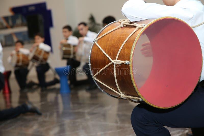 El instrumento nacional del nagara de Azerbaijan niños en trajes nacionales jugar los tambores El jugar azerí joven de los indivi fotografía de archivo libre de regalías