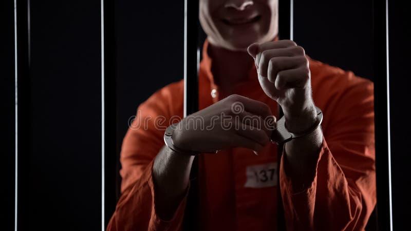 El intentar criminal desbloquear las esposas, colocándose detrás de barras, escape de la prisión imagen de archivo libre de regalías