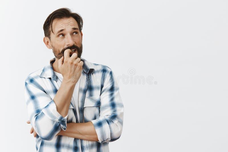 El intentar del hombre calcula cómo sobreviva hasta la cheque siguiente, la uña penetrante y mirar fijamente en la esquina superi imagenes de archivo