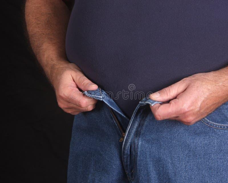 El intentar masculino gordo abotonar sus pantalones vaqueros foto de archivo
