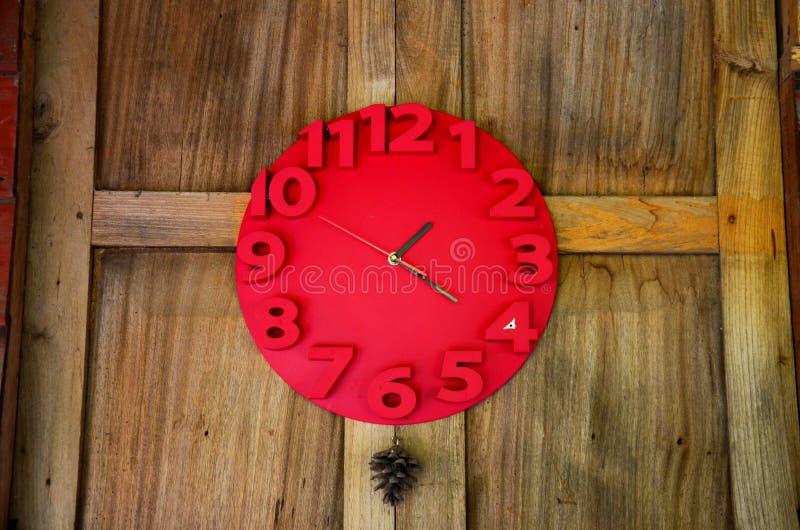 El interior adorna con el reloj rojo en la pared de madera fotografía de archivo libre de regalías
