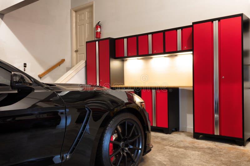 El interior casero del garaje organizó altamente y limpio con el coche parqueado foto de archivo