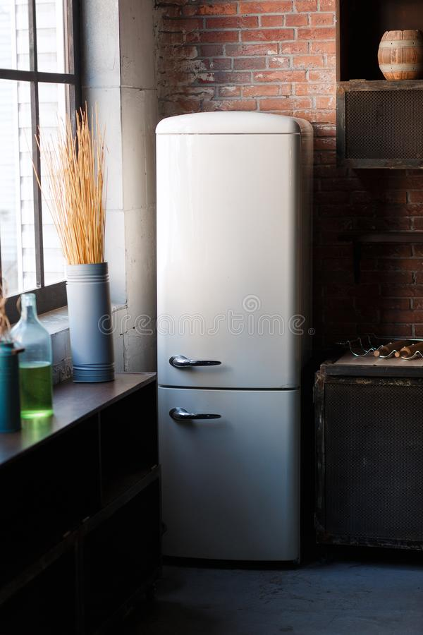 El interior de la cocina en oscuridad texturizó colores con el refrigerador retro moderno blanco, la decoración rústica de la par foto de archivo