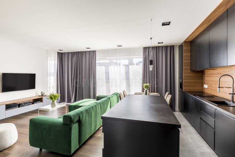 El interior de la habitación con el salón verde, aparato de TV, ventanas con cubre y esquina de la cocina del espacio abierto fotos de archivo