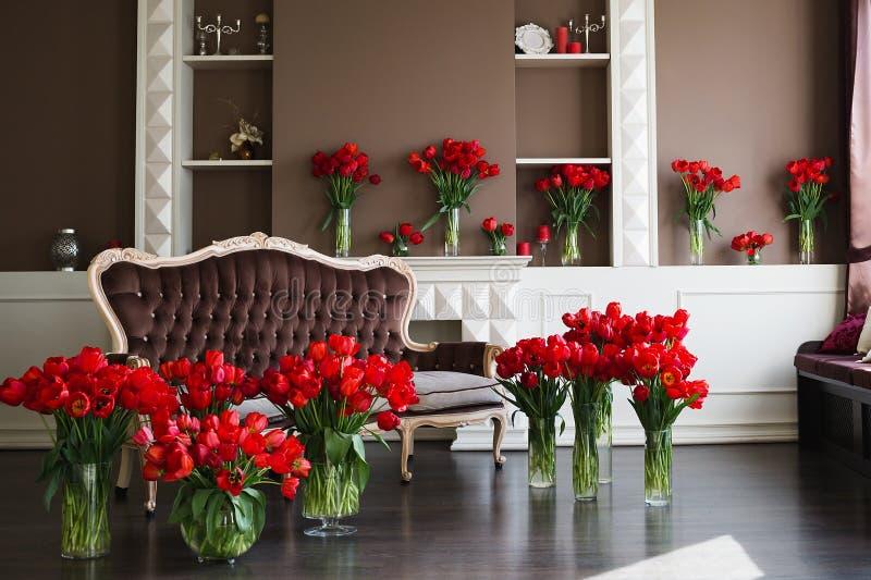 El interior de la sala de estar en tonos marrones con los ramos grandes de tulipanes rojos en floreros imágenes de archivo libres de regalías