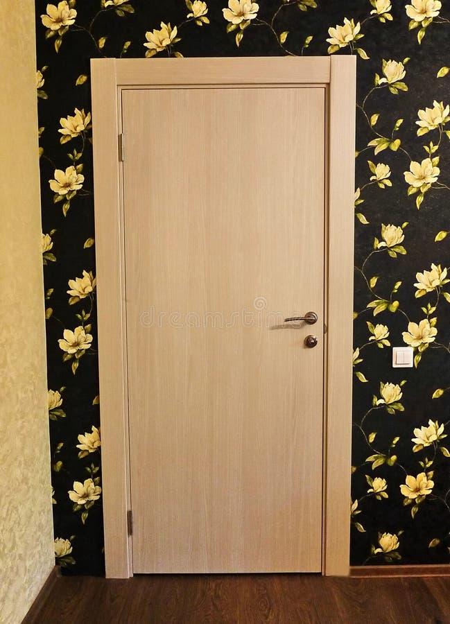 El interior de un cuarto instalado con un nuevo interior Puerta La puerta instalada armonioso complementa el interior del cuarto, fotografía de archivo