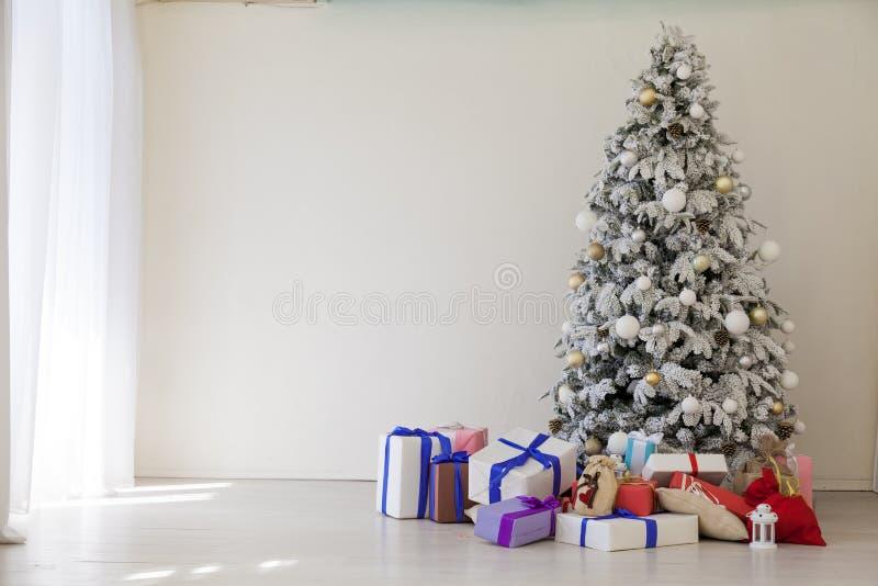 El interior del cuarto blanco con los regalos de un árbol de navidad y de la Navidad imagen de archivo