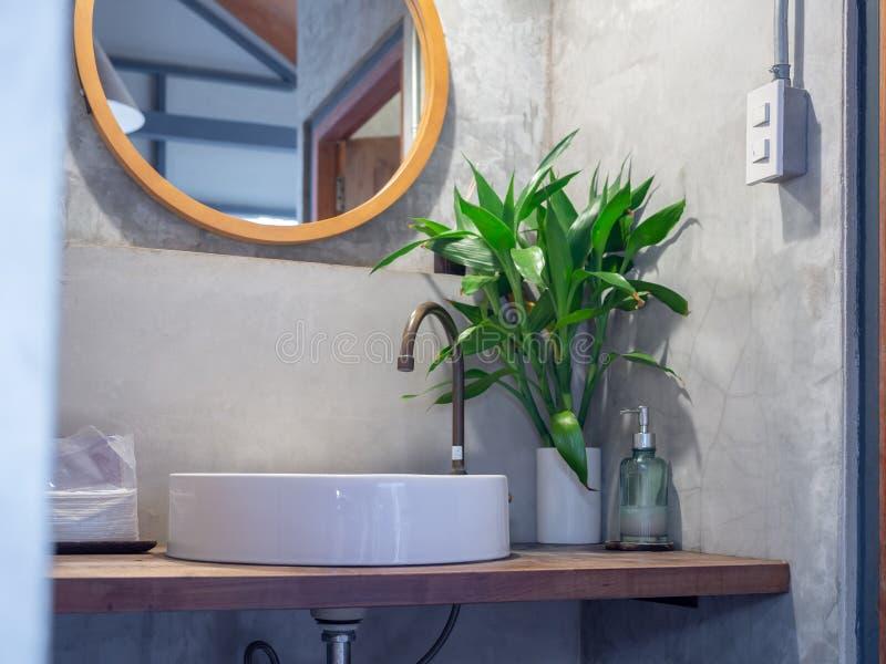 El interior del cuarto de baño de estilo loft Fauceta de latón con lavabo blanco, hojas verdes en jarrón de cerámica y botella de fotografía de archivo