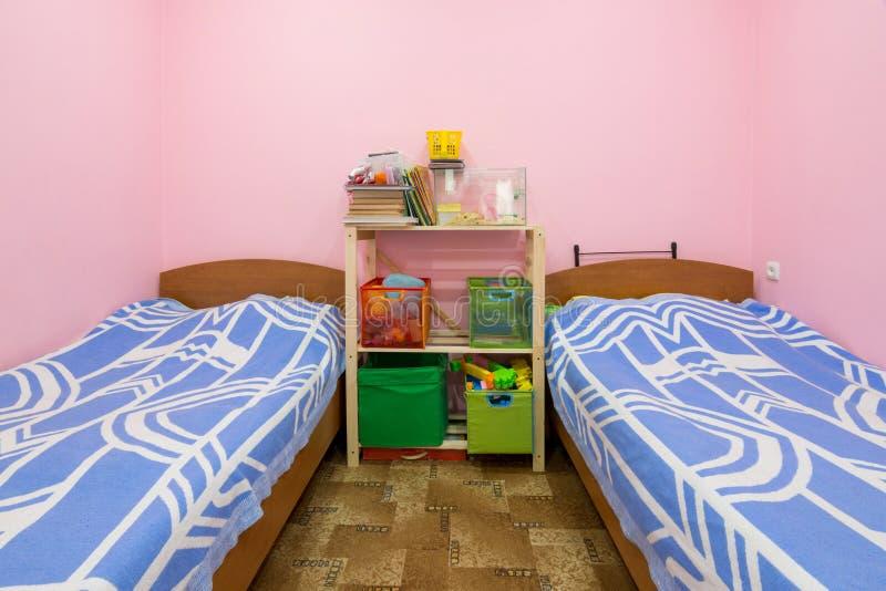 El interior del pequeño sitio del dormitorio con dos camas y un estante hecho en casa en el centro fotografía de archivo libre de regalías