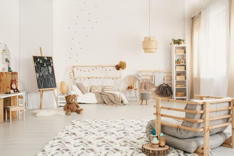 El interior del sitio del ` s del niño con un peluche refiere el piso, pizarra, imagen de archivo