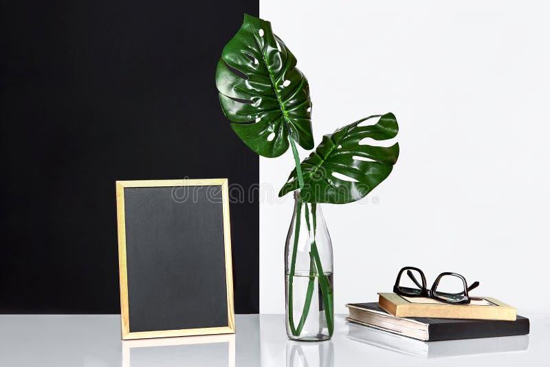 El interior elegante con mofa encima del marco del cartel, hojas en la botella de cristal en la tabla con la pared blanco y negro imágenes de archivo libres de regalías