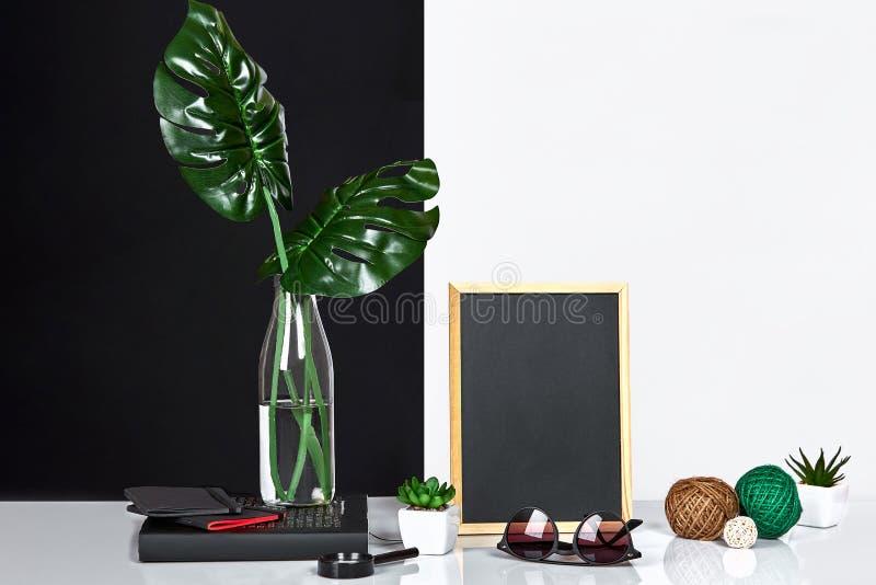 El interior elegante con mofa encima del marco del cartel, hojas en la botella de cristal en la tabla con la pared blanco y negro imagenes de archivo