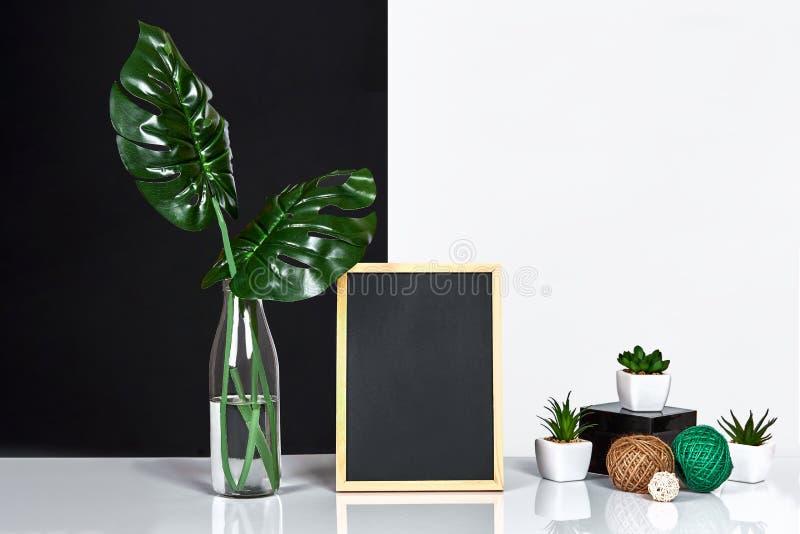 El interior elegante con mofa encima del marco del cartel, hojas en la botella de cristal en la tabla con la pared blanco y negro fotos de archivo libres de regalías