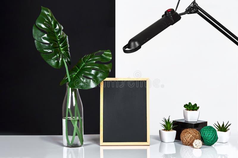 El interior elegante con mofa encima del marco del cartel, hojas en la botella de cristal en la tabla con la pared blanco y negro fotografía de archivo libre de regalías