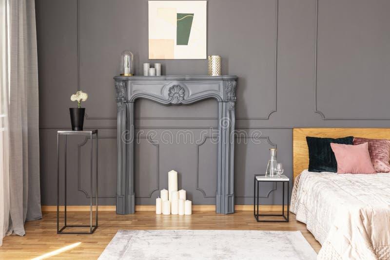 El interior elegante del dormitorio con velas fijó en un porta de la chimenea fotografía de archivo