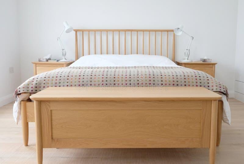 El interior inspirado escandinavo del dormitorio que mostraba los muebles de madera del dormitorio, blanco pintó las paredes, el  foto de archivo libre de regalías